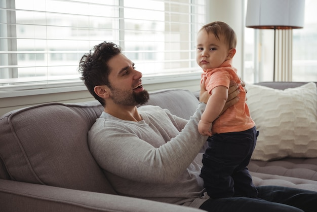 Father playing with his baby on sofa in living room