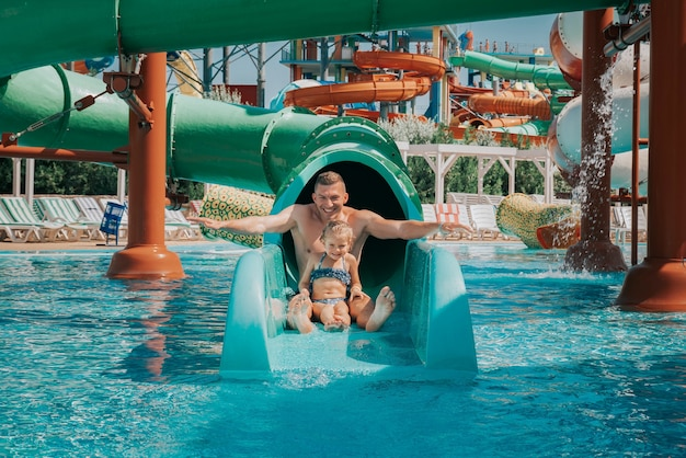 Father playing with his daughter in swimming pool funny family weekend father and daughter enjoy time together in water park