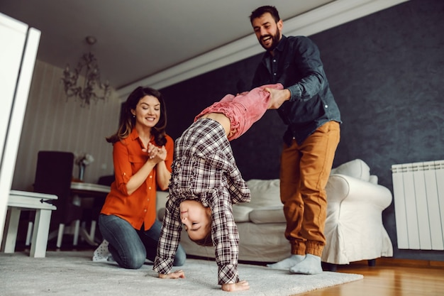 Father playing with his daughter and teaching her how to make headstand. mother kneeling next to them and watching with smile on her face