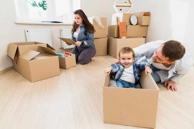 Father playing with his son and his wife unpacking the cardboard box at background