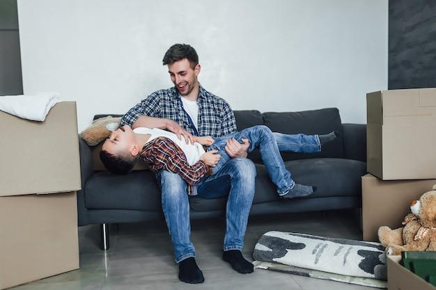 新しいモダンな家で息子と遊んでいる父。陽気な感情