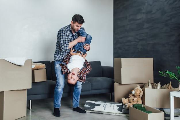 新しいモダンな家で息子と遊ぶ父