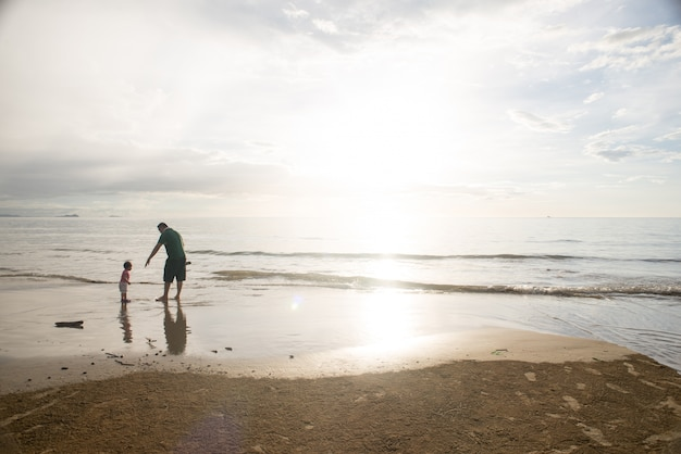 Father playing with his son on the shore