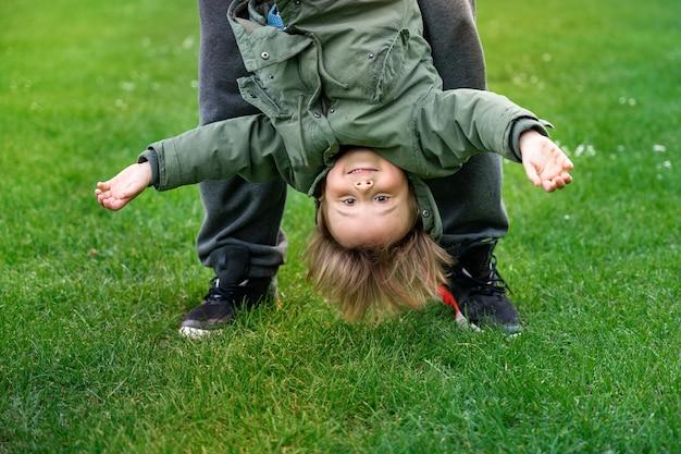 Отец играет с маленьким сыном на открытом воздухе на траве. мальчик малыша качается вверх ногами. счастливый ребенок в парке. концепция активного воспитания.