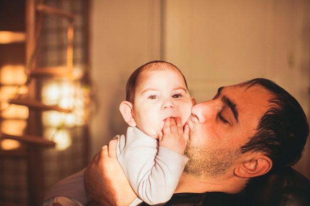 Father playing with son and kissing baby holding him in her arms