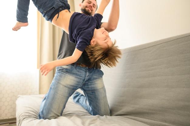 Отец играет с сыном на диване