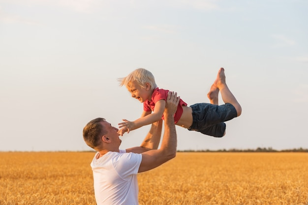 Отец играет с сыном на открытом воздухе в поле