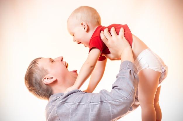 공기에서 그를 들어 올리는 유아 아들을 노는 아버지