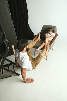自宅の居間で幼い息子と遊ぶ父