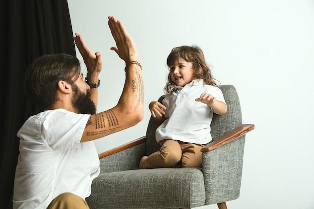 Padre che gioca con il giovane figlio nel salotto di casa. giovane papà che si diverte con i suoi figli in vacanza o nel fine settimana. concetto di genitorialità, infanzia, festa del papà e relazione familiare.