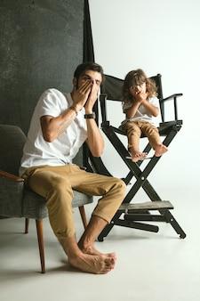 Padre che gioca con il giovane figlio nel salotto di casa. giovane papà divertendosi con i suoi figli in vacanza o nel fine settimana. concetto di genitorialità, infanzia, festa del papà e rapporto familiare.