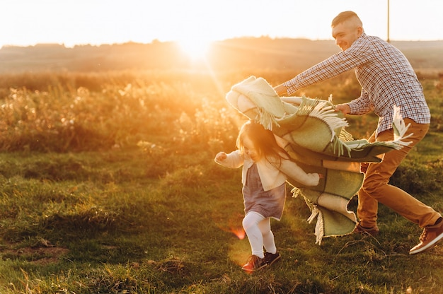 Father plays with his little daughter in the green field at sunset