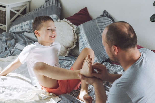 父はベッドで息子と7-10で遊ぶ。お父さんは子供の足をくすぐります。家族、楽しんで