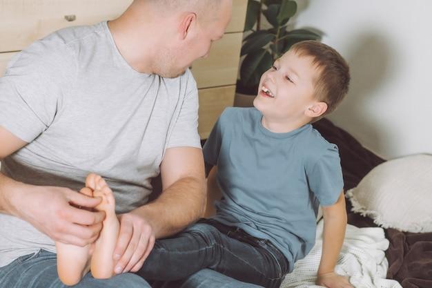 父は床に座っている息子と7-10で遊んでいます。お父さんは子供の足をくすぐります。家族、楽しんで