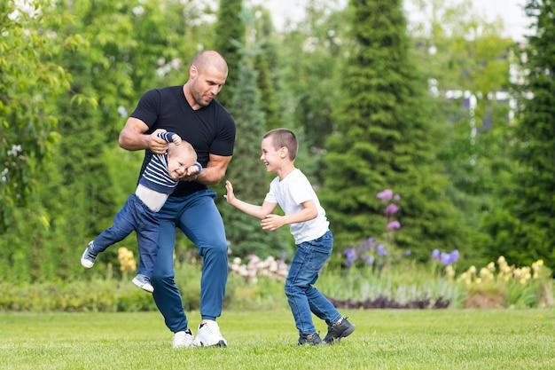 Отец играет с маленьким сыном мальчика, обнять ребенка в парке в теплый летний день.