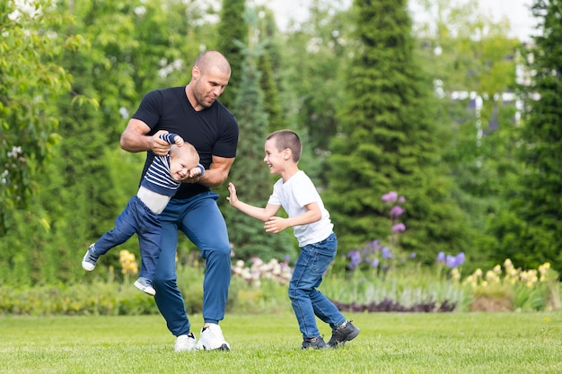 Father  plays with little boy son, hug baby  in the park on a warm summer day.