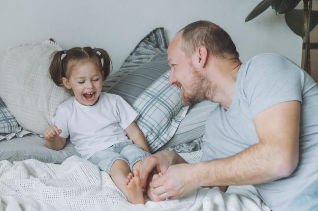아버지는 침대에서 어린 딸 2-4와 놀아요. 아빠는 아이들의 발을 간질입니다. 가족, 재미