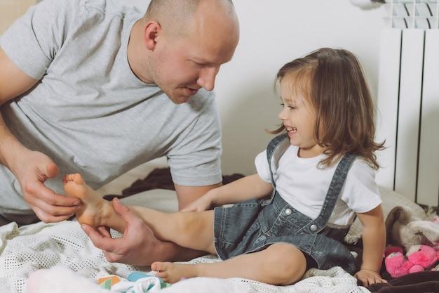 父は床で幼い娘と2-4で遊ぶ。お父さんは子供の足をくすぐります。家族、楽しんで