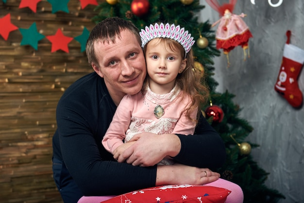 The father plays with a little daughter who sits on a chair near the tree by the fireplace.