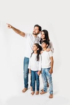 白い背景の上に妻と子供たちと一緒に立っている間、父は人差し指。セレクティブフォーカス