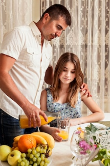 Father pouring juice for daughter at dinner table