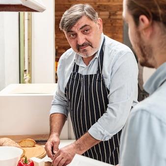 Отец готовит обед и смотрит на сына