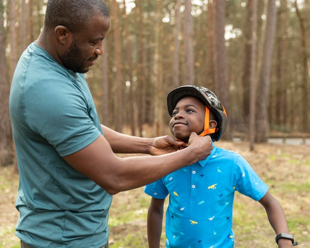 Father preparing his kid for a bicycle ride