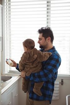 부엌에서 그의 아기를 위해 우유를 준비하는 아버지
