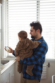 Padre che prepara il latte per il suo bambino in cucina