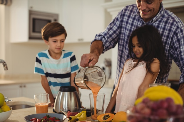 Father preparing smoothie with his kids in kitchen