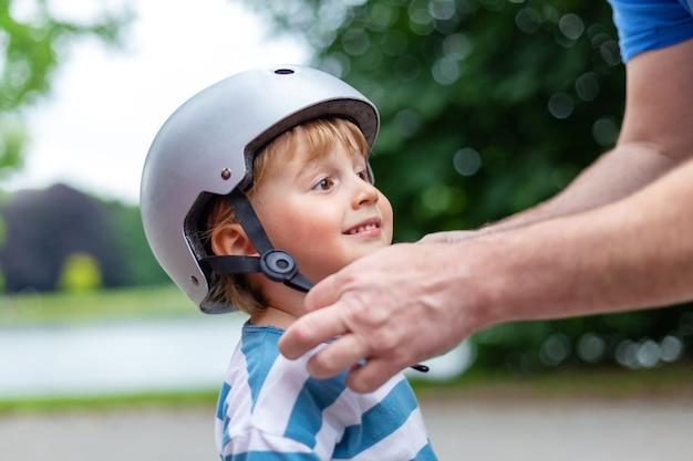 아버지는 공원에서 스쿠터, 자전거 타기 및 롤러 블레이드를 위해 웃는 소년에게 안전 헬멧을 착용합니다.