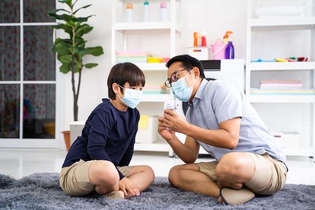 아버지는 집에서 코로나바이러스 검역소에서 아들 의료용 안면 마스크를 착용합니다.
