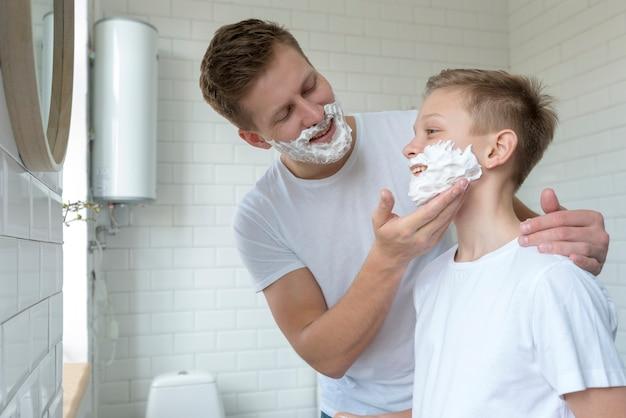 Отец наносит крем для бритья на лицо сына