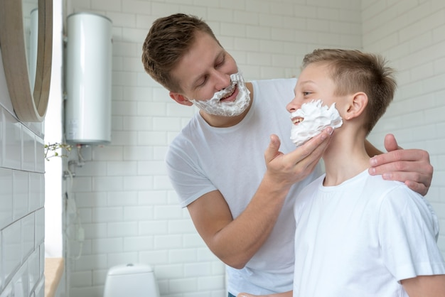Father puts shaving cream on son's face