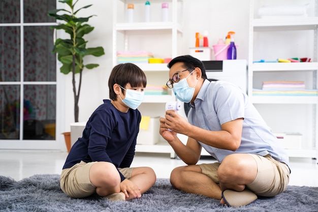 Father puts on son medical face mask inhome coronavirus quarantine