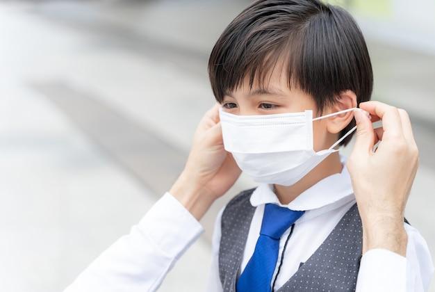 彼の息子に保護マスクを置く父、保護のためにフェイスマスクを身に着けているアジアの家族