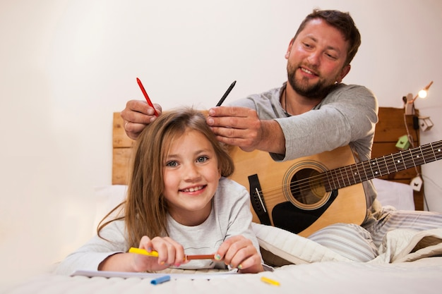 Father putting crayons on his daughter's head