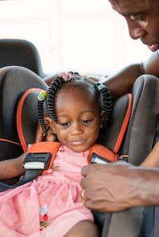 Padre che mette sua figlia su una sedia per auto per bambini