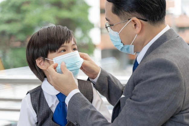 Father putting a protective mask on his son ,asian family wearing face mask for protection during the quarantine coronavirus covid 19 outbreak