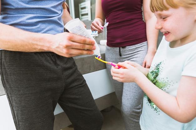 父親が娘の筆に練り歯磨きを塗る