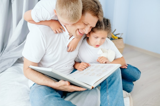 Отец читает книгу своим детям, дочери и сыну