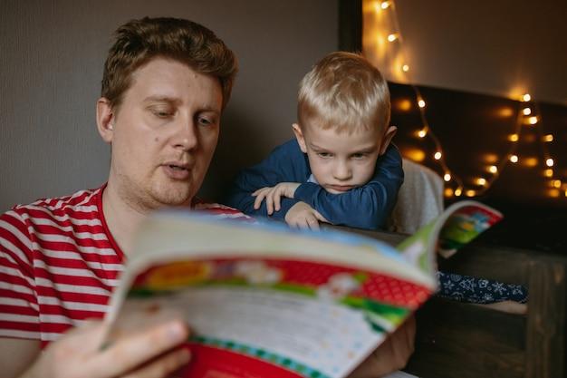 그의 귀여운 작은 아들 새해 축하에 크리스마스 책을 읽는 아버지