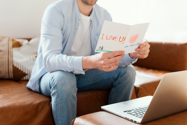 Отец читает дневную открытку своего отца во время работы на ноутбуке