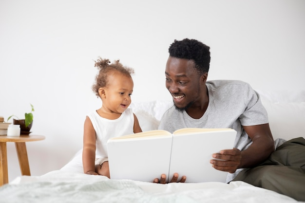 彼女の女の赤ちゃんに読んでいる父