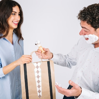 Father receive present from daughter during shaving
