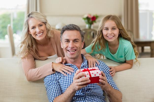 Отец получает подарок от своей дочери и жены в гостиной