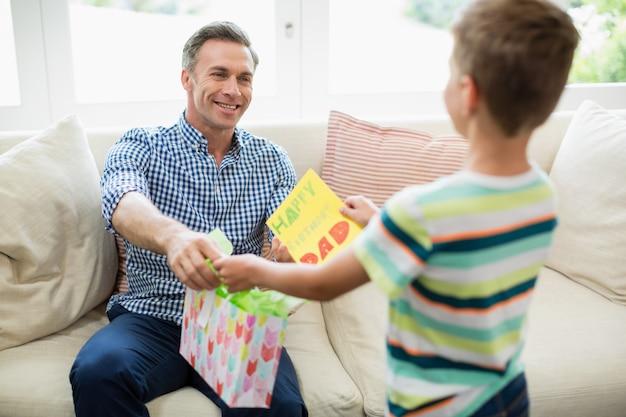 아버지는 거실에서 그의 아들로부터 선물을 받고