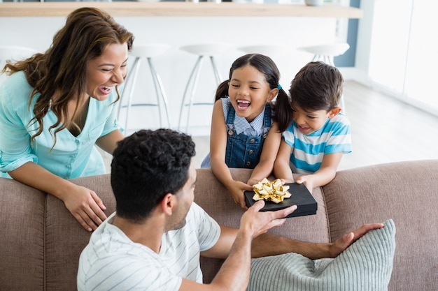 Father receiving a gift from his kids and wife in living room