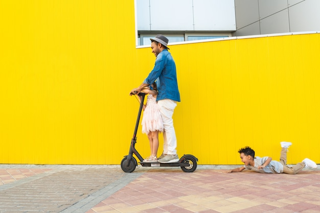 Father riding an electric scooter with his kids.