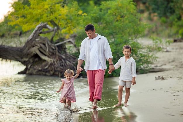 父の日。幸せな日焼けした男が彼の子供たちと娘と息子と一緒に川岸に沿って歩きます。